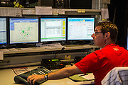 A male Belgian traffic controller monitors tram traffic flow on the Ghent tramway network in the De Lijn control centre, Ghent, Belgium.
