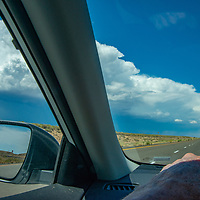 A car speeds along Interstate 70 in Utah, under a building thunderhead.