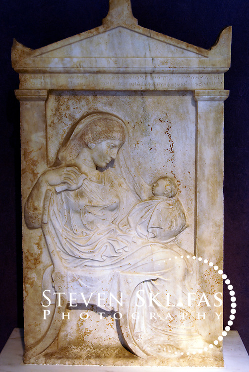 """Grave relief of Ampharete holding her infant grandchild. 430-420 BC. Kerameikos museum. Athens. Greece. On the epistyle is the epigram: """"I hold here the beloved child of my daughter, which I held on my knees when we were alive and saw the light of the sun, and now, dead, I hold it dead"""". Serving as a burial ground as long ago as the 12th century BC, Kerameikos located in the ancient neighbourhood of potters contains part of the ancient city walls and the Dipylon, the main gate of Ancient Athens at a junction of the Sacred Way and Panathenaic Way. It served as a burial ground for the richest and most distinguished citizens of the city."""