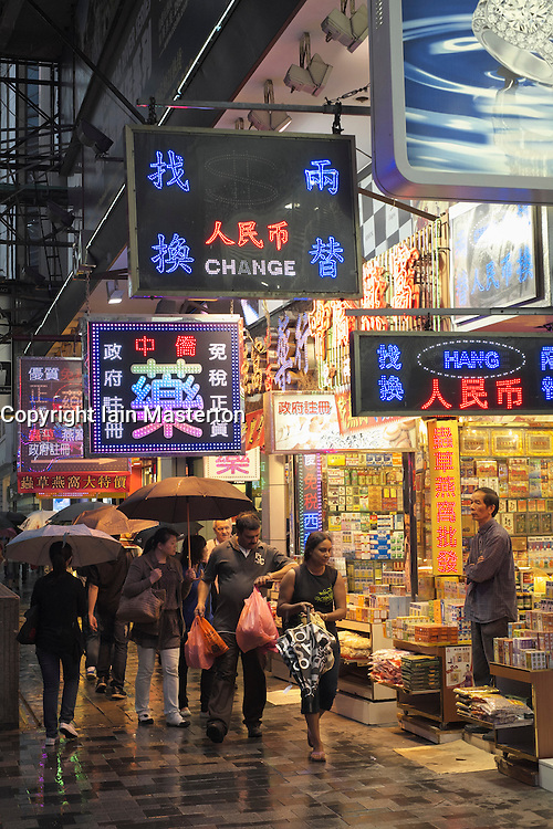 Shoppers on Nathan Road in the rain at night in Kowloon Hong Kong
