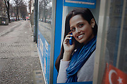 The poster of an Asian-looking model advertisies a telecoms company services in an internet store window<br /> in Wedding, a north-western district of Berlin. Speaking on her smartphone. the lady smiles with the grim background of this area of Berlin, home to immigrants and a population of non-Germans.