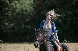 Young woman riding galloping horse in farm and smiling, Bavaria, Germany