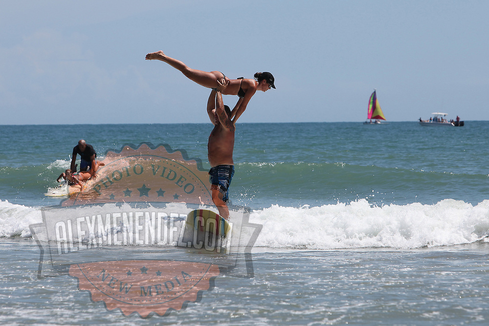 A tandem surfing couple performs at the 28th annual National Kidney Foundation, Rich Salick Pro/Am surf festival takes place at the the Cocoa Beach pier on Saturday,  September 2, 2013 in Cocoa Beach, Florida. This event raises thousands of dollars for people with kidney disease and also benefits the services of the NKF of Florida. (AP Photo/Alex Menendez)