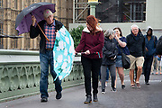 A woman struggles with an umbrella during heavy rain fall and windy weather on Westminster Bridge in London, United Kingdom on 16th August 2019.