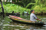 """17 NOVEMBER 2012 - BANGKOK, THAILAND:  A woman paddles her small canoe through a khlong or canal in the Thonburi section of Bangkok. Bangkok used to be known as the """"Venice of the East"""" because of the number of waterways the criss crossed the city. Now most of the waterways have been filled in but boats and ships still play an important role in daily life in Bangkok. Thousands of people commute to work daily on the Chao Phraya Express Boats and fast boats that ply Khlong Saen Saeb or use boats to get around on the canals on the Thonburi side of the river. Boats are used to haul commodities through the city to deep water ports for export.    PHOTO BY JACK KURTZ"""