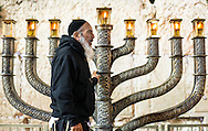 A man next to a menorah at the Western Wall in Jerusalem on the 7th day of Hanukkah. Hanukkah, also known as the Festival of Lights, is an eight-day Jewish holiday commemorating the rededication of the Holy Temple in Jerusalem. The festival is observed by the kindling of the lights of a unique candelabrum, the nine-branched menorah or hanukiah, one additional light on each night of the holiday, progressing to eight on the final night.<br /> <br /> This image was published on the Telegraph in UK on 9 Dec 2019 https://www.telegraph.co.uk/news/0/history-hanukkah-miracle-oil-sparked-jewish-festival-lights/