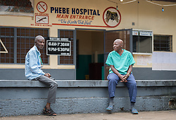 2 November 2019, Ganta, Liberia: Two men rest outside the entrance of Phebe Hospital. Located in Bong county, Phebe Hospital serves tens of thousands of patients each year. It is a government referral hospital for which the Lutheran Church in Liberia provides managerial resources.