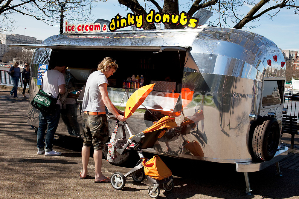 Stopping for ice cream and doughnuts at the Dinky Doughnuts Airstream caravan stall along the Southbank on a spring afternoon, London. South Bank is an area of London, England located immediately adjacent to the south bank of the River Thames. It forms a long and narrow section of riverside development that is within the London Borough of Lambeth and partly in the London Borough of Southwark. It developed much more slowly than the north bank of the river due to adverse conditions, and throughout its history has twice functioned as an entertainment district, separated by a hundred years of use as a location for industry. The South Bank is a significant arts and entertainment district.