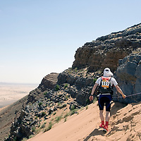 26 March 2007:  #527 Ghislain Marcoux of Canada reaches summit of jebel El Otfal, 947 meters and an average 25% slope, with the help of a cord, during the second stage (21.7 miles) of the 22nd Marathon des Sables between Khermou and jebel El Otfal. The Marathon des Sables is a 6 days and 151 miles endurance race with food self sufficiency across the Sahara Desert in Morocco. Each participant must carry his, or her, own backpack containing food, sleeping gear and other material.