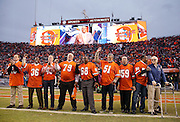 """Sports analyst Tom Jackson is shown on the Sports Authority Field at Mile High stadium scoreboard while addressing fellow members (including L-R Randy Gradishar, Billy Thompson, Steve Foley, Rubin Carter, Barney Chavous, Bob Swenson, Joe Rizzo, Larry Evans, and head coach Red Miller) of the 1977 Denver Broncos defense nicknamed """"Orange Crush"""" as they are honored at halftime during the Denver Broncos NFL week 19 AFC Divisional Playoff football game against the Indianapolis Colts on Sunday, Jan. 11, 2015 in Denver. The Colts won the game 24-13. ©Paul Anthony Spinelli"""