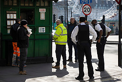 © Licensed to London News Pictures. 24/03/2020. London, UK. Police keep their distance as they queue with others at a taxi drivers take away cafe near Trafalgar Square after Prime Minister Boris Johnson announced that the UK will now lockdown in order to fight the spread of the coronavirus. Only essential journeys for food and one period of excercise will be allowed per day. Photo credit: Peter Macdiarmid/LNP