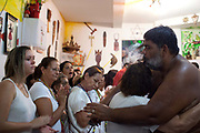 Master of ceremonies; Babalawo hugs one of the adherants at a Ceremony at Terreiro (yard) peace and love / Terreiro Paz y Amor, Salvador, Bahia, Brazil. Often the lines between Candomble, Catholicism and Umbanda are blurred. Salvador de Bahia is seen as the home of Candomble.