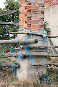 corner of a with plastic rope and old wood created fence