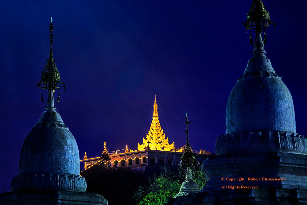 Magical Mandalay: Light beams strike Mandalay Hill as it is bathed in the vibrant blue of sunset, viewed from between the Stupas of the Kuthodaw Pagoda, Mandalay Myanmar.