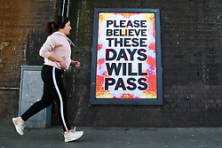 © Licensed to London News Pictures. 05/04/2020. London, UK. A woman walks past 'PLEASE BELIEVE THESE DAYS WILL PASS' sign in north London during a pandemic outbreak of the coronavirus. Photo credit: Dinendra Haria/LNP