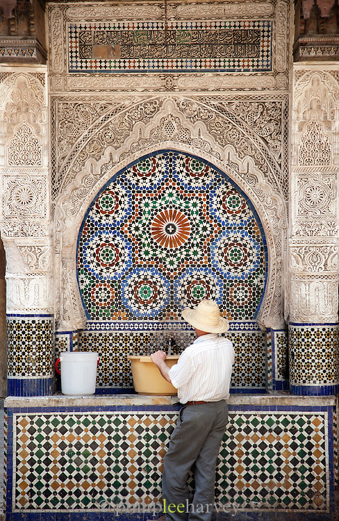A man filling a bucket of water from a public fountain at the Nejjarine Museum in the medina, Fes, Morocco