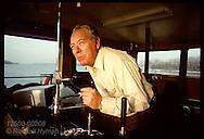 Captain Lloyd Eneix pilots the towboat Cooperative Venture along the Mississippi River; St. Louis Missouri
