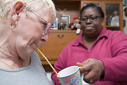 Carer assisting a woman with cerebral palsy to drink a cup of tea,