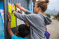 AREQUIPA, PERU - APRIL 7, 2014: Volunteer teacher posting signs in the door of one the schools of HOOP Peru in the community of Flora Tristan. HOOP Peru is a NGO fully committed to breaking the cycle of poverty by empowering the Flora Tristan families through enhancing their education.