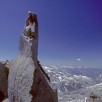 """A climber stands on the """"Milk Bottle,"""" the summit of 14,040+ foot Starlight Peak onthe Palisade Crest of California's Sierra Nevada.  Kings Canyon National Park stretches in the background."""