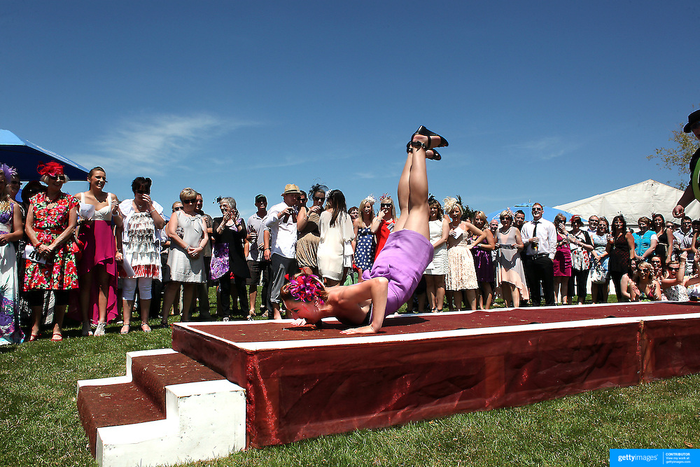 """A lady performs 'The Worm"""" during Fashions in the Field during a day at the Races at Ascot Park, Invercargill, Southland, New Zealand. 10th December 2011. Photo Tim Clayton"""