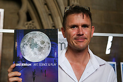 © Licensed to London News Pictures. 15/08/2021. Bristol, UK. Luke Jerram holds his latest book 'Art, Science & Play' at Bristol Cathedral. Luke Jeram's Moon installation in Bristol Cathedral. Measuring seven metres in diameter, the Museum of the Moon features detailed NASA imagery of the lunar surface. At an approximate scale of 1:500,000 each centimetre of the internally lit spherical sculpture represents 5 km of the moon's surface. The Museum of the Moon  is open until 30 August 2021. Photo credit: Dinendra Haria/LNP