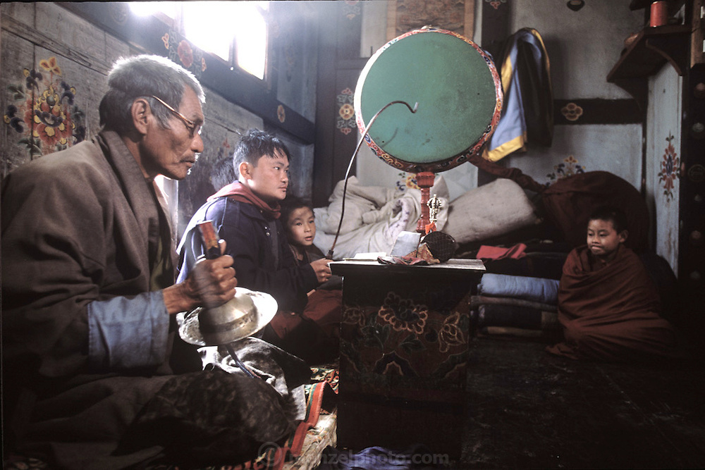 (MODEL RELEASED IMAGE). Namgay, a village elder (at left), and Chato Namgay, his 14-yearold monk son (at far right) perform a greeting ceremony with visiting monks in the family prayer room at the beginning of the village electricity celebration. (Supporting image from the project Hungry Planet: What the World Eats.) The Namgay family living in the remote mountain village of Shingkhey, Bhutan, is one of the thirty families featured, with a weeks' worth of food, in the book Hungry Planet: What the World Eats.