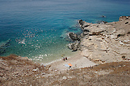 Greece, Koufonissi, Cyclades: A couple sitting in the beach