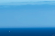A sailboat,dwarfted by the expanse of blue sky and ocean off the Oregon coast, near Yachats.