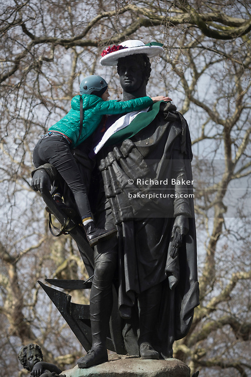 A womens group member drapes a suffragette-style sash across the statue of Francis, Duke of Bedford on International Womens' Day, on 8th March 2018, in Russell Square, London, England. According to the group concerned about the poor representation of women commemorations, there are fewer than 3% of non-royal statues in the UK. Francis Russell, 5th Duke of Bedford (1765-1802) was an English aristocrat and Whig politician, responsible for much of the development of central Bloomsbury, London.