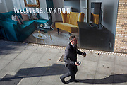 A Londoner dashes to a bus beneath a marketing billboard for The Levers - a new apartment development on the Walworth Road at Elephant And castle, on 25th September 2018, in Southwark, London, England. The Levers (A Peabody development) will be a complex of 1,2,and 3 bed flats close to Elephant & Castle and Elephant Park - both undergoing major redevelopment.