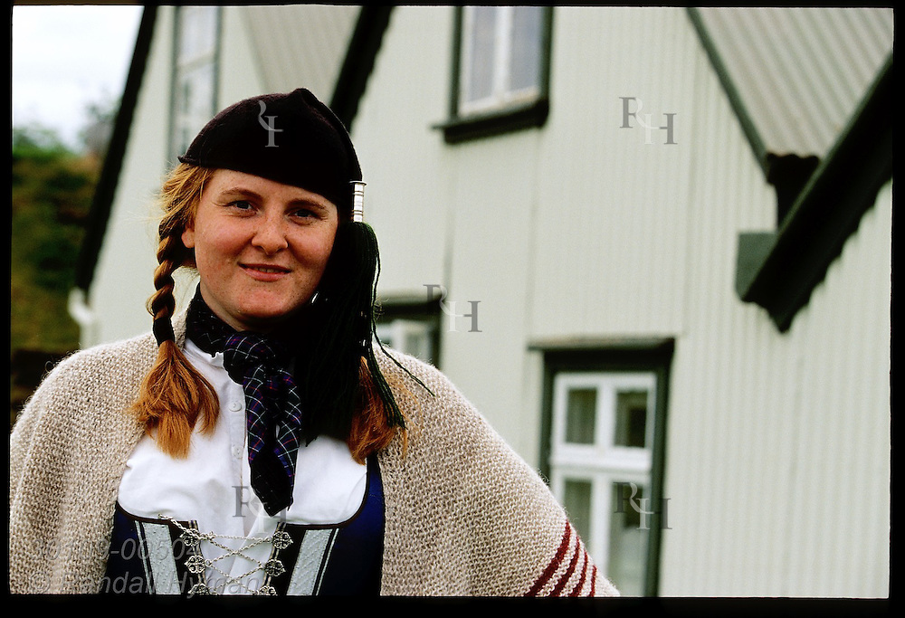 Woman in national costume stands outside one of many relocated historic buildings at Arbaer Open Air Museum; Reykjavik, Iceland