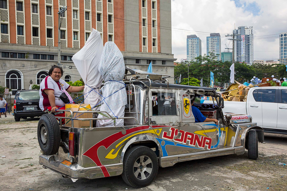 People on a Jeepney preparing for the Grand Marian Parade in Intramuros, Metro Manila, Philippines. In the background, some of the floats built to celebrate the Feast of the Immaculate Conception that are part of the procession can be seen.
