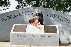 © Licensed to London News Pictures. 06/06/2014. National Memorial Arboretum, Alrews, Staffordshire, UK. The D Day service at the Normandy Memorial, National Memorial Arbouretum. Pictured, Normandy Veteran Rev Dick Sargent (90), holding the flag that he took on the landing craft on the beaches on D Day, today taking part in the sevice at the N.M.A. Photo credit : Dave Warren/LNP