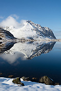 Mountains reflect into calm water of a lake.