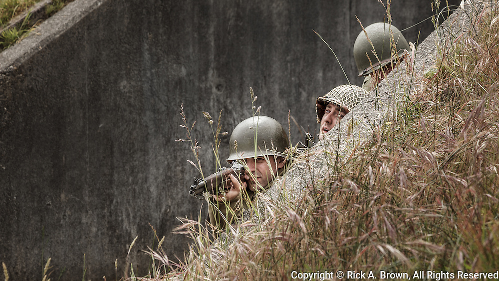 USA, Oregon, Astoria, Ft. Stevens State Park, living historian infantry soldiers in fighting position behind cover.