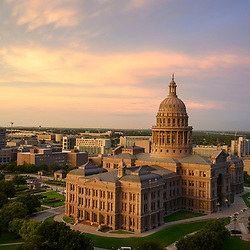 A summer sunrise shines over the Texas Capitol in downtown Austin as Lone Star State battle the coronavirus going into its sixth month of pandemic. Legislators will return to Austin in early January facing major budget shortfalls and pandemic related crises.