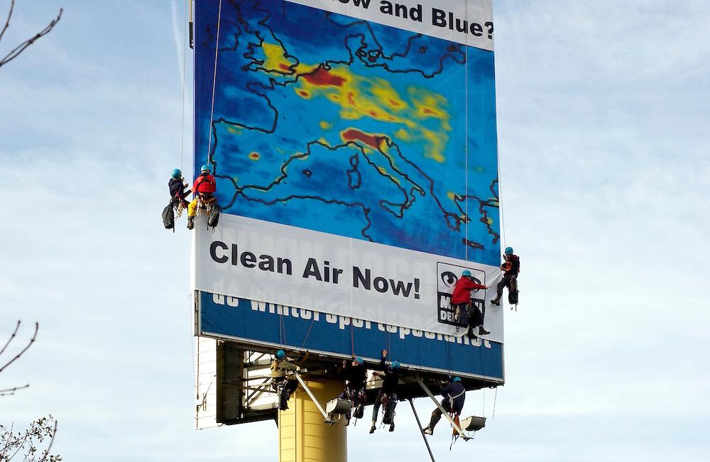 Rotterdam, 23 nov 2004.Klimmers van Milieudefensie hebben  langs de A20 in Vlaardingen een spandoek opgehangen dat de recente satellietbeelden van de luchtvervuiling in Europa weergeeft. Het reusachtige doek draagt de leus Who's afraid of red, yellow and blue? Clean air now! Hiermee start een campagne om de aanleg van de A4 Midden-Delfland en Tweede Coentunnel tegen te houden. In opdracht van Milieudefensie gaan onderzoekbureaus de luchtkwaliteit meten. Volgens Milieudefensie zijn er nu al te veel uitlaatgassen in de lucht om te voldoen aan de Europese wetten voor luchtkwaliteit.