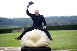 © Licensed to London News Pictures. 14/09/2018. HARROGATE, UK. Graham Barratt of Gloucester poses for photographs with his winning Giant Pumpkin of 319.8kg. Harrogate Autumn Flower Show runs from 14-15 September with over 5,000 blooms and an expected attendace of 60,000 visitors at the Yorkshire Showground in Harrogate..  Photo credit: Nigel Roddis/LNP