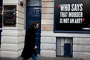"People passing a poster which reads "" Who says that murder is not an art?"" outside the Garrick Theatre in the West End Theatreland district of London."