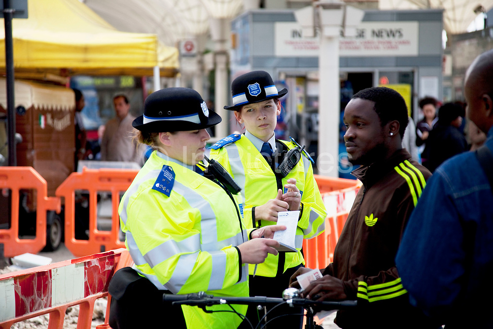 Man is cautioned by Community Police Officers in Stratford in East London. This is a relatively poor area of London, but in recent years has seen much regeneration, the construction of a major transport hub and various shopping complexes. Stratford is adjacent to the London Olympic Park and is currently experiencing regeneration and expansion linked to the 2012 Summer Olympics. (Photo by Mike Kemp/For The Washington Post)
