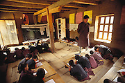 English lesson in classroom at the school in Gaselo, Bhutan. Nalim's daughter Bangam is in attendance (though out of frame). Children in Bangam's class range from 6 to 17 in age, some of who travel several hours to attend. The school is an hour walk from their home in Shingkhey, Bhutan. From Peter Menzel's Material World Project.