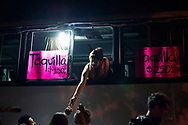 A woman works from a bus parked outside a concert venue, selling tequila from the window, in Oaxaca, Mexico.