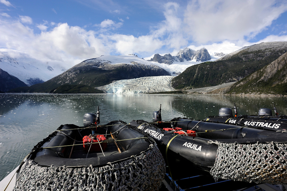 Inflatable Zodiacs in front of both branches of  Pia Glacier in Garibaldi Fjord off the Strait of Magellan. Garibaldi Fjord, Strait of Magellan, Republic of Chile. 22Feb13..