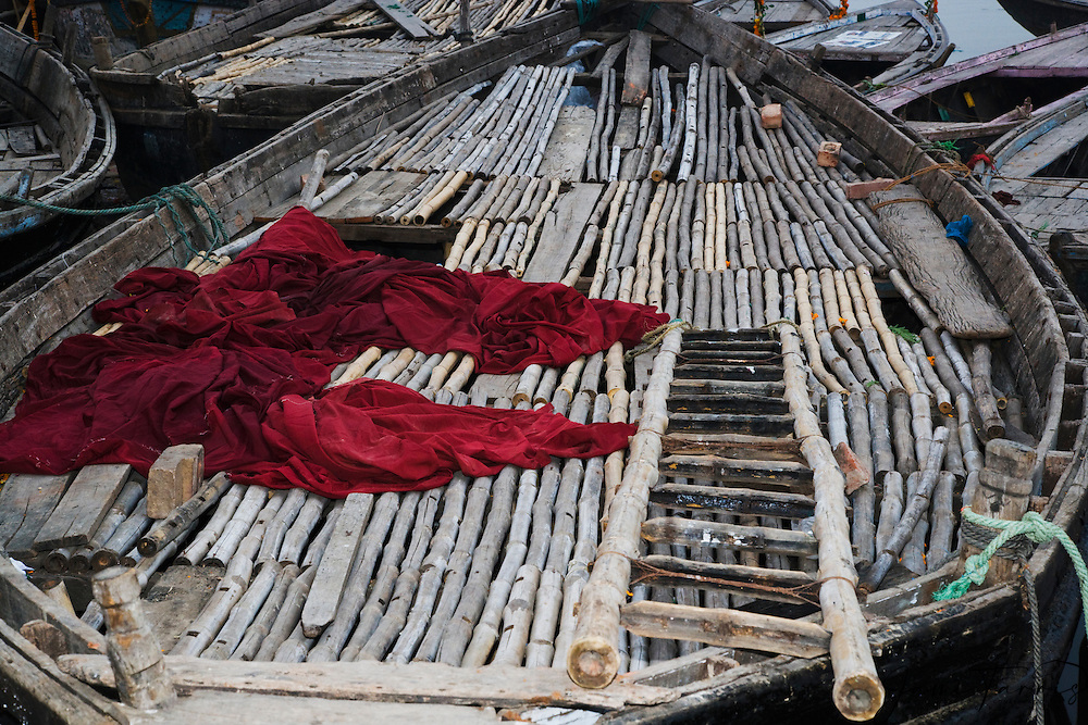 View down on a red tunic thrown on an old wooden boat on the Ganges River, Varanasi, Uttar Pradesh, India