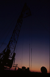 Stock photo of the silhouette of an on-shore rig at sunset