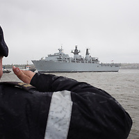 LIVERPOOL, UK, 23rd May, 2013. A member of the Royal Navy salutes HMS Bulwark as she arrives in the River Mersey, Liverpool, UK, as part of the Battle of the Atlantic 70th anniversary celebration weekend. A fleet of 21  Royal Naval vessels will visit over the weekend.