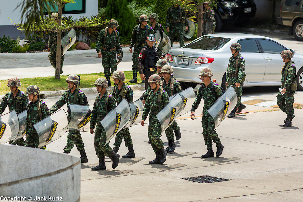 """20 MAY 2104 - BANGKOK, THAILAND:   Thai soldiers carry their riot shields while they to take up positions at the Army Club to prevent protestors from entering the club grounds after the declaration of martial law. The Thai Army declared martial law throughout Thailand in response to growing political tensions between anti-government protests led by Suthep Thaugsuban and pro-government protests led by the """"Red Shirts"""" who support ousted Prime Minister Yingluck Shinawatra. Despite the declaration of martial law, daily life went on in Bangkok in a normal fashion. There were small isolated protests against martial law, which some Thais called a coup, but there was no violence.  PHOTO BY JACK KURTZ"""