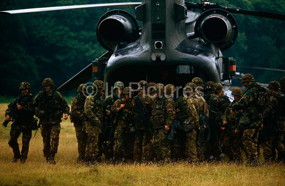 German troops are ready to embark into a stationary Chinook helicopter during battle exercises in east Anglia, England. Waiting for the signal to climb aboard, they wear full battle-dress and camouflage for the English forest. Joining a joint force of British and foreign regiments, these Germans are distinctive by their helmets, still shaped much like their WW2 counterparts.