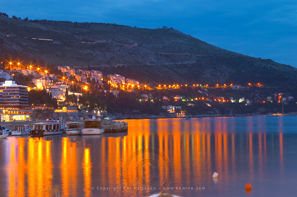 The old harbour with evening city light reflections in the water in evening blue light Dubrovnik, old city. Dalmatian Coast, Croatia, Europe.